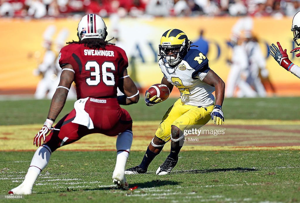 Running back Vincent Smith #2 of the Michigan Wolverines runs the ball as defender D.J. Swearinger #36 of the South Carolina Gamecocks closes in for the tackle during the Outback Bowl Game at Raymond James Stadium on January 1, 2013 in Tampa, Florida.