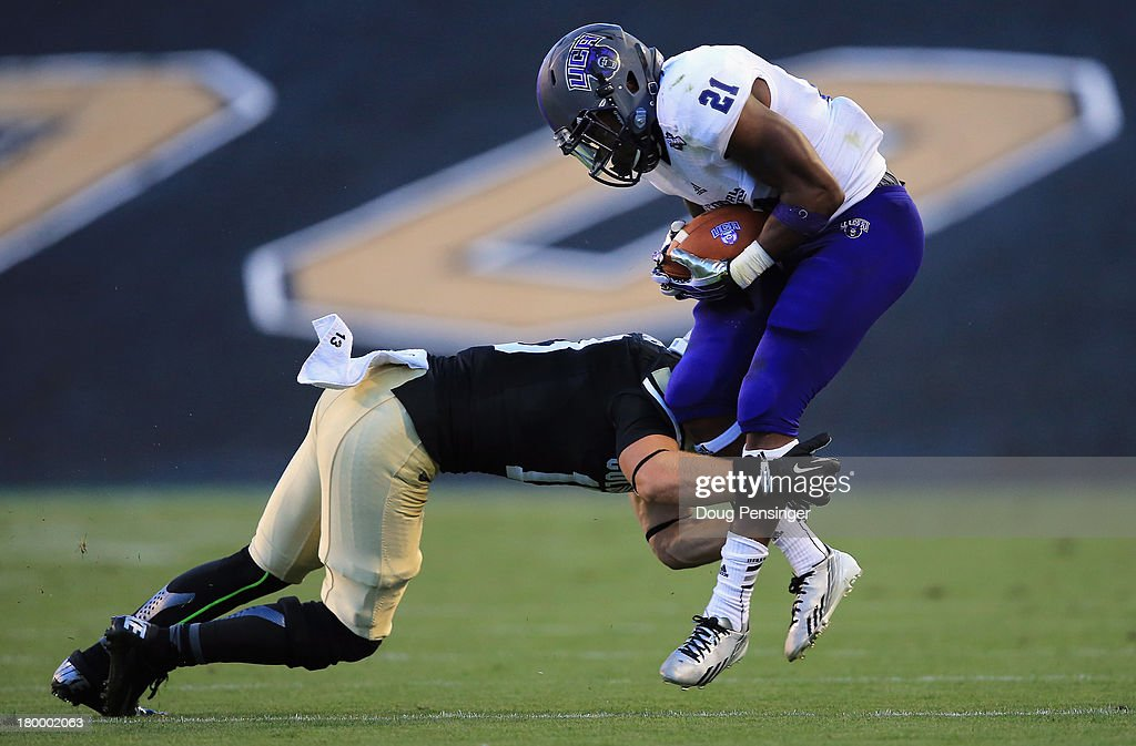Running back Willie Matthews #21 of the Central Arkansas Bears makes a pass reception and is tackled by defensive back Parker Orms #13 of the Colorado Buffaloes at Folsom Field on September 7, 2013 in Boulder, Colorado.