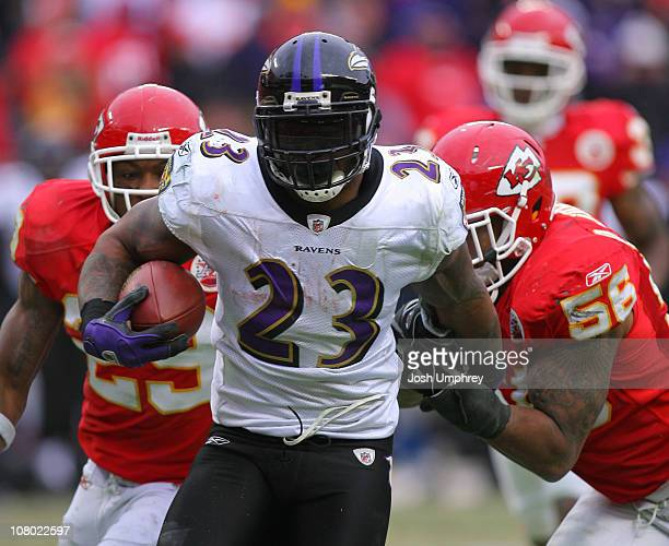 Running back Willis McGahee of the Baltimore Ravens breaks away from safety Eric Berry and linebacker Derrick Johnson of the Kansas City Chiefs and...