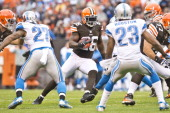 Running back Willis McGahee of the Cleveland Browns runs a play while under pressure from strong safety Glover Quin and cornerback Chris Houston of...
