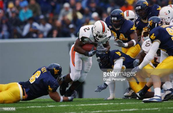 Running back Willis McGahee of the University of Miami Hurricanes is tackled by linebacker Grant Wiley of the West Virginia University Mountaineers...