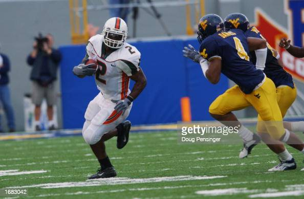 Running back Willis McGahee of the University of Miami Hurricanes runs the ball while being defended by Lewis Daniels of the West Virginia University...