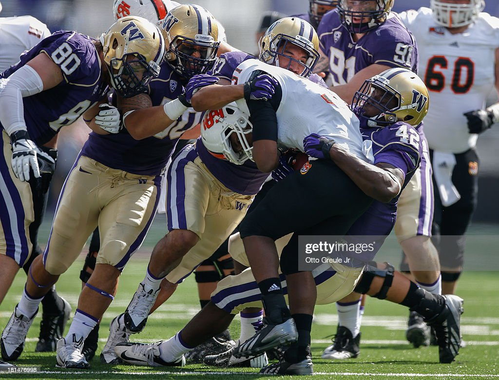 Running back Xavier Finney #31 of the Idaho State Bengals is tackled by members of the Washington Huskies on September 21, 2013 at Husky Stadium in Seattle, Washington. The Huskies defeated the Bengals 56-0.