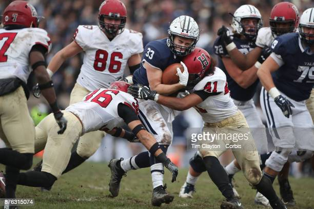 Running back Zane Dudek of Yale is tackled by Charlie Walker of Harvard and Tanner Lee of Harvard during the Yale V Harvard Ivy League Football match...