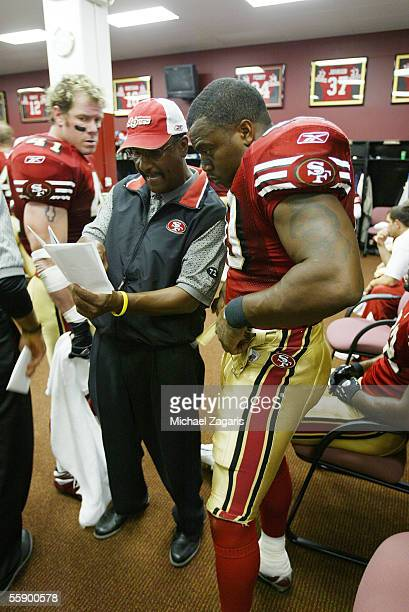 Running backs coach Bishop Harris meets with fullback Fred Beasley of the San Francisco 49ers in the locker room at halftime during the game against...