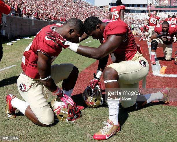 Running backs James Wilder Jr #32 and Karlos Williams Sr #9 of the Florida State Seminoles pray together before the game against the Maryland...