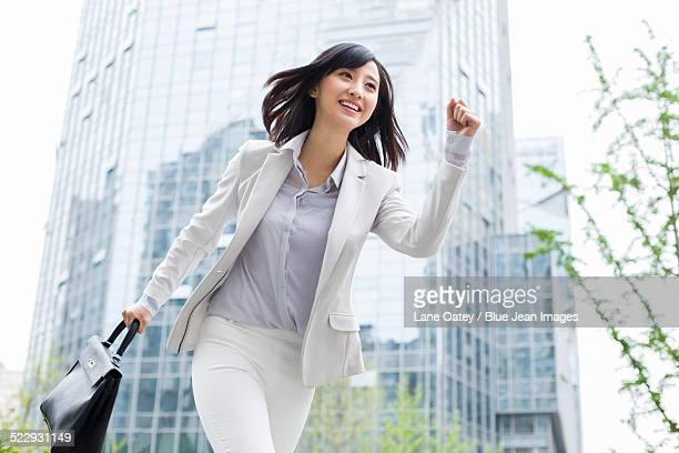 Running businesswoman with briefcase in hand