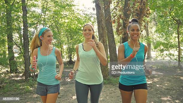 Running club exercising on dirt trail together in park