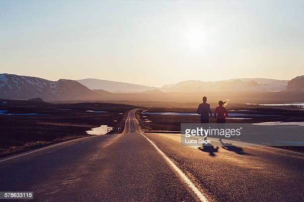 Running couple on road towards sunlit mountains