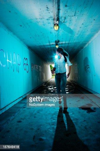 Running girl looking backwards in tunnel