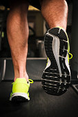 Close-up on the legs of a man doing fitness indoor