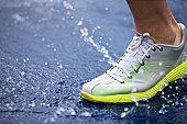 Running shoe splashing water on track