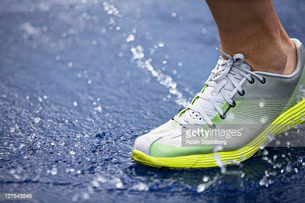 Running shoe splashing water on track