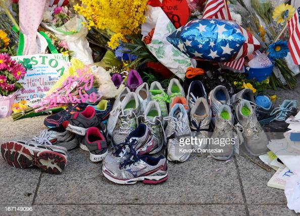 Running shoes are placed at a makeshift memorial for victims near the finish line of the Boston Marathon bombings at the intersection of Boylston...