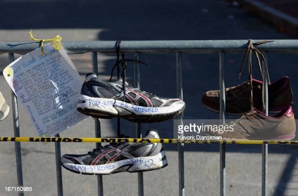 Running shoes are placed at a makeshift memorial for victims near the finish line of the Boston Marathon bombings at the intersection of Newbury...