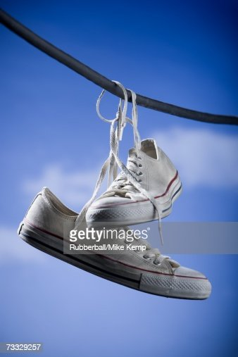Running shoes hanging on wire outdoors with blue sky