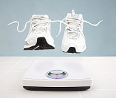 Running shoes hovering above bathroom scale