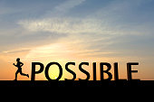 The word possible is silhouetted against a bright sunset sky. To the left of the word is a single human figure running towards the left of the image. The sky is orange at the bottom changing to blue a