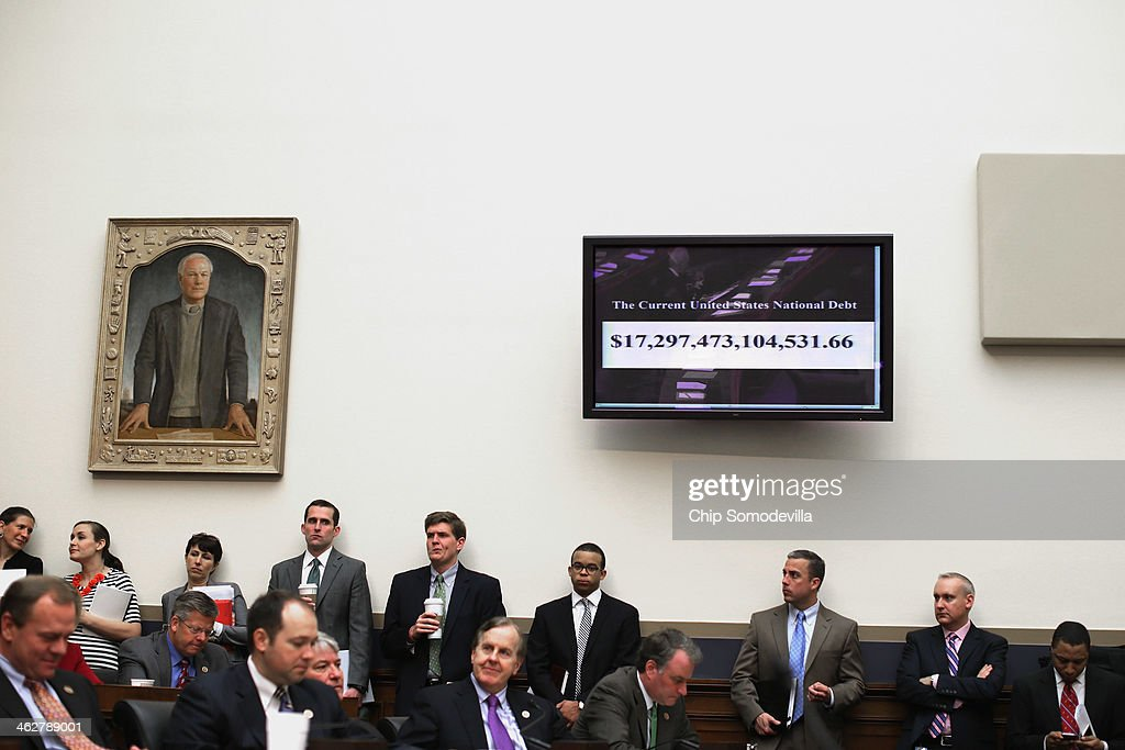 A running tally of the US national debt is displayed on a television during a House Financial Services Committee hearing about the Volker Rule in the...