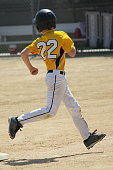 A young boy running the bases in a youth baseball game.