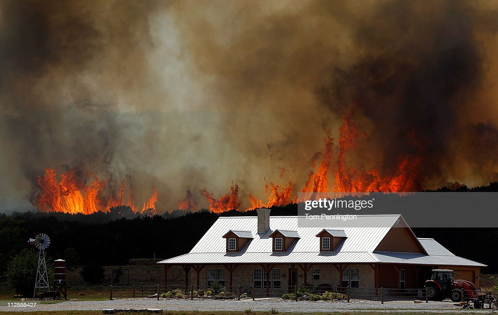 A running wildfire threatens a home on April 19, 2011 in Strawn, Texas. Dozens of area homes have been destroyed in the wildfires that have been fueled by dry conditions, high winds, and low humidity.