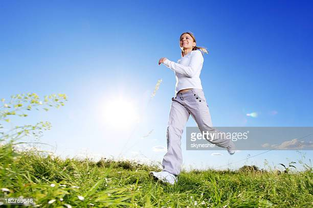 Running woman against the blue sky