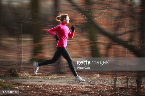 Running woman in focus with blurred woodland background : Stock Photo
