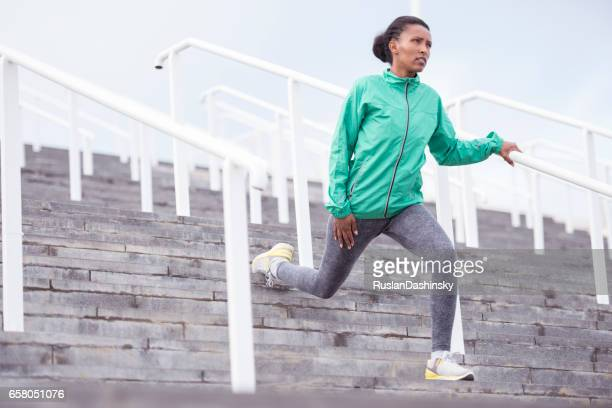 Running woman stretching her legs standing on stairs, holding handrail.