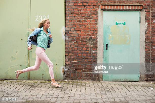 Running young woman in front of industrial building