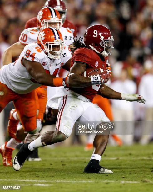 Runningback Bo Scarbrough of the Alabama Crimson Tide attempts to avoid a tackle by Defensive Tackle Carlos Watkins of the Clemson Tigers during the...