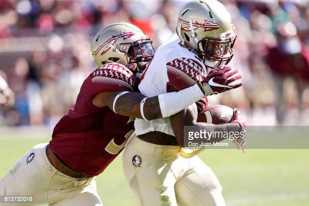 Runningback Cam Akers is tackled by Defensive Back Derwin James of the Florida State Seminoles during the annual Garnet and Gold Spring Football game...