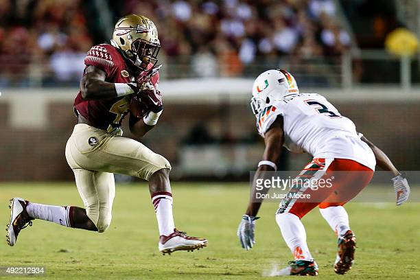 Runningback Dalvin Cook of the Florida State Seminoles avoids a tackle by Cornerback Tracy Howard of the Miami Hurricanes during the game at Doak...