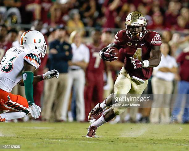 Runningback Dalvin Cook of the Florida State Seminoles avoids a tackle by Safety Rayshawn Jenkins of the Miami Hurricanes during the game at Doak...