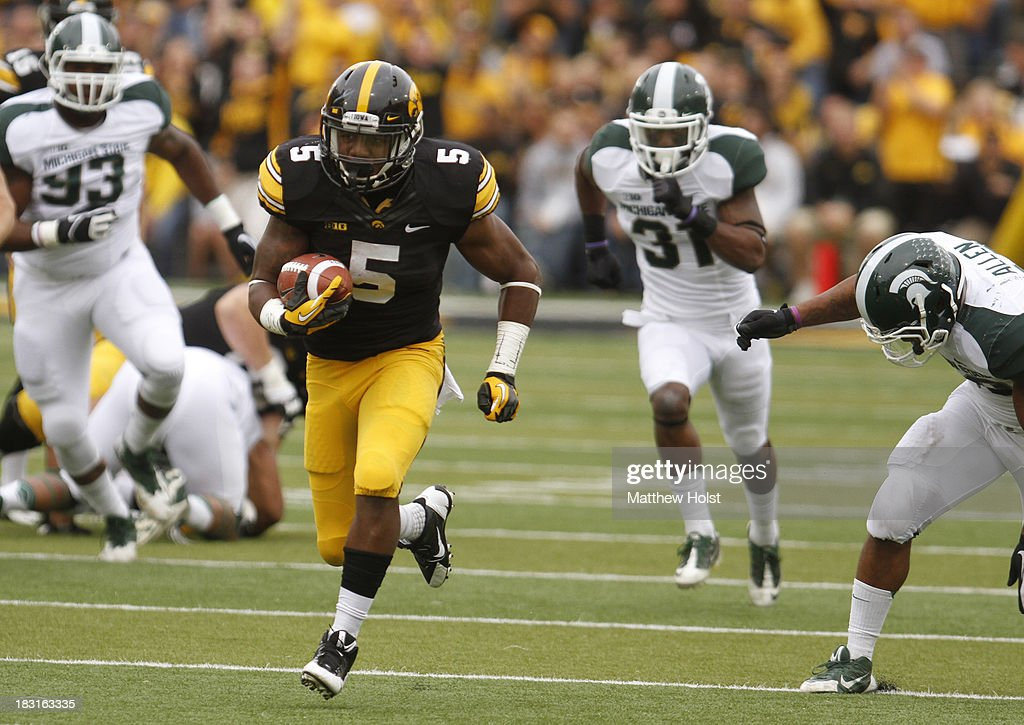 Runningback Damon Bullock #5 of the Iowa Hawkeyes rushes up field during the second quarter past linebacker Denicos Allen #28 of the Michigan State Spartans on October 5, 2013 at Kinnick Stadium in Iowa City, Iowa.