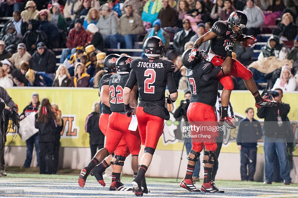 Runningback David Oku #25 of the Arkansas State Red Wolves celebrates with teammates after scoring a touchdown during their game against the Kent State Golden Flashes on January 6, 2013 at Ladd-Peebles Stadium in Mobile, Alabama. Arkansas State defeated Kent State 17-13.