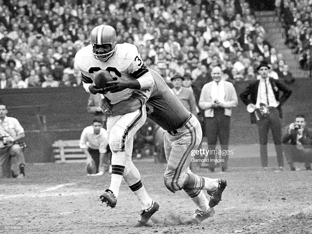 Runningback Jim Brown of the Cleveland Browns tries to shake a tackle during a game on November 15 1964 against the Detroit Lions at Municipal...