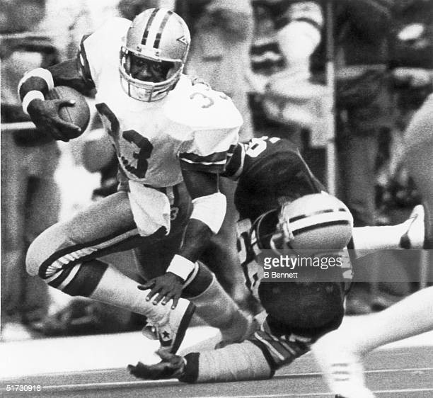 Runningback Tony Dorsett of the Dallas Cowboys runs through the arms of John Anderson of the Green Bay Packers during a game on January 16 1983 in...
