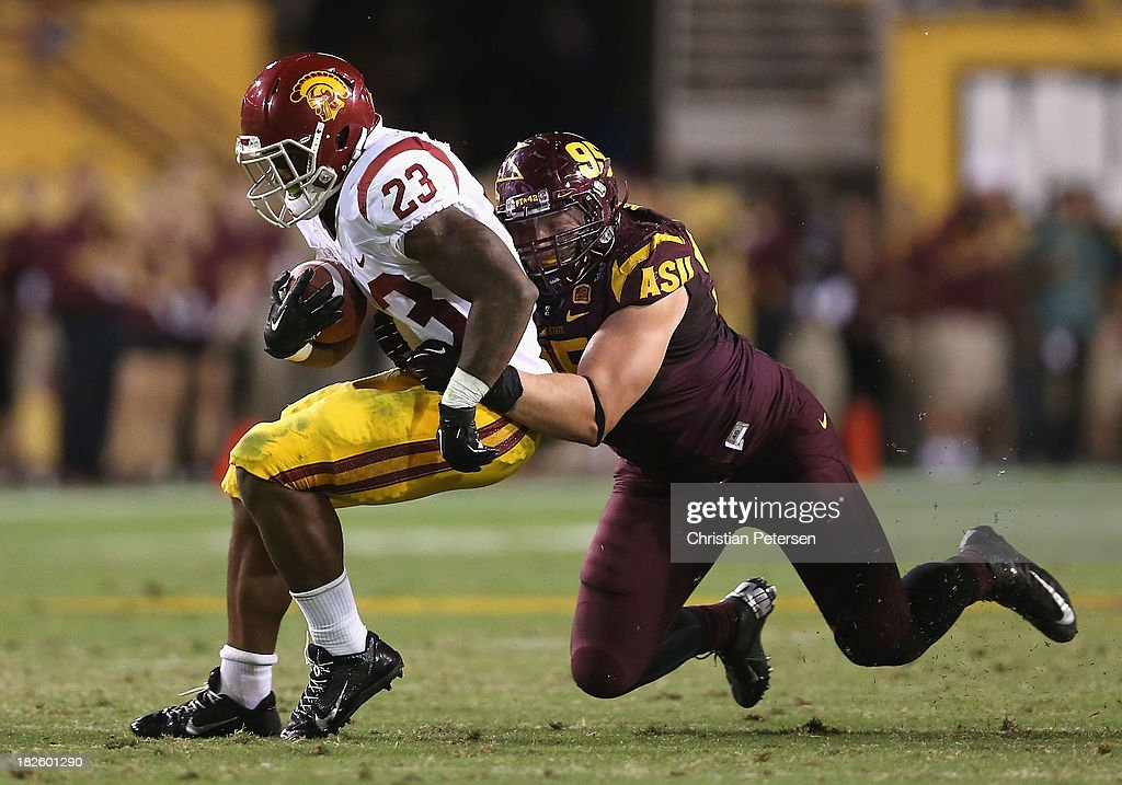 Runningback Tre Madden #23 of the USC Trojans is tackled by defensive end Gannon Conway #95 of the Arizona State Sun Devils Arizona State Sun Devils he rushes the football during the college football game at Sun Devil Stadium on September 28, 2013 in Tempe, Arizona. The Sun Devils defeated the Trojans 62-41.