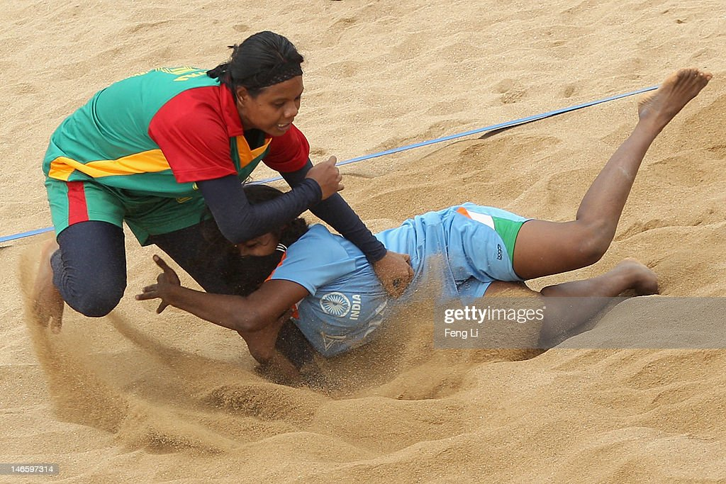Rupali Akhtar (L) of Bangladesh is held by Marshalmary Savariyappan of India during the Beach Kabaddi Women's Team Group A match between India and Bangladesh on Day 4 of the 3rd Asian Beach Games Haiyang 2012 at Fengxiang Beach on June 20, 2012 in Haiyang, China.