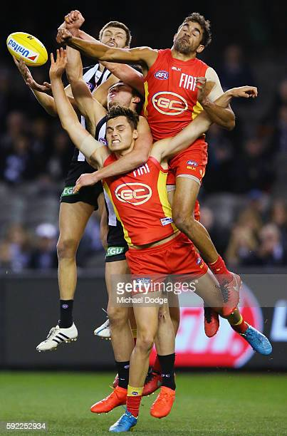 Rupert Wills of the Magpies compete for the ball against Kade Kolodjashnij and Jack Martin of the Suns during the round 22 AFL match between the...