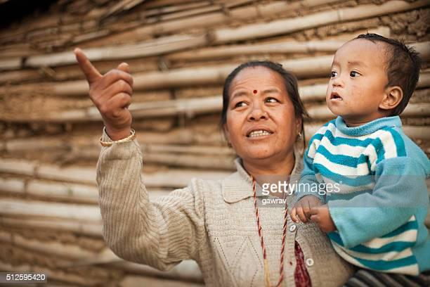 Rural asiatique femme montrant quelque chose à son petit-fils regardant loin.
