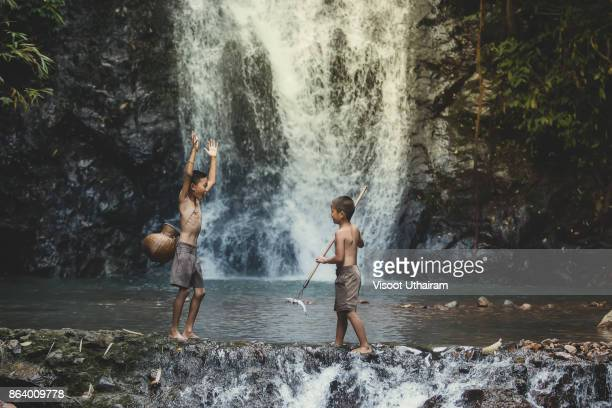 Rural children are fishing in the river at forest