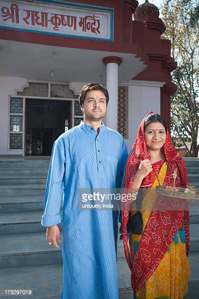 Rural couple standing in front of a temple, Sohna, Haryana, India
