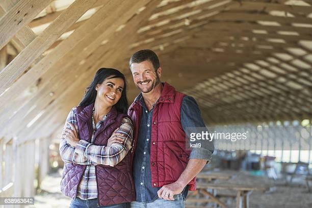 Rural couple standing inside farm building