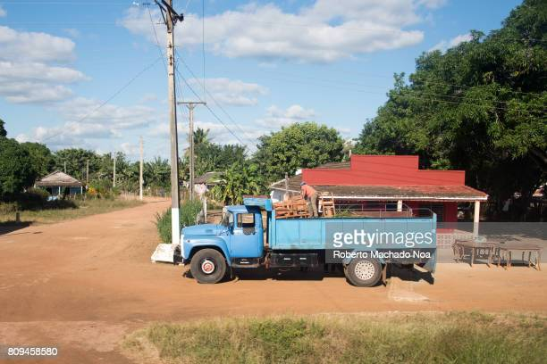 Rural everyday lifestyle Man loading furniture in back of a blue V8 Russian truck parked on a dirt road