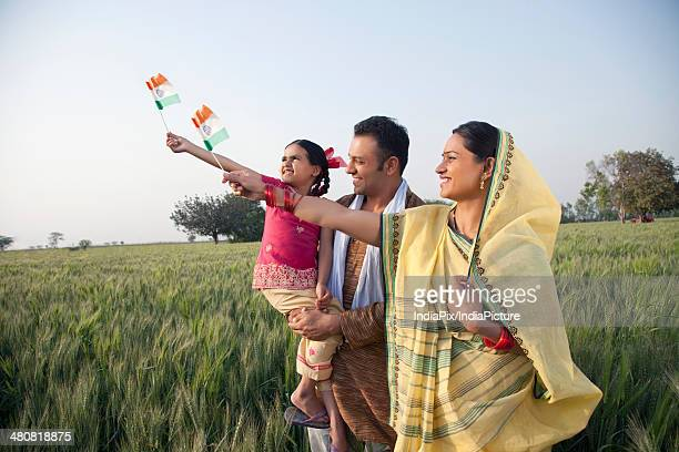 Rural family holding Indian flag while standing in farm