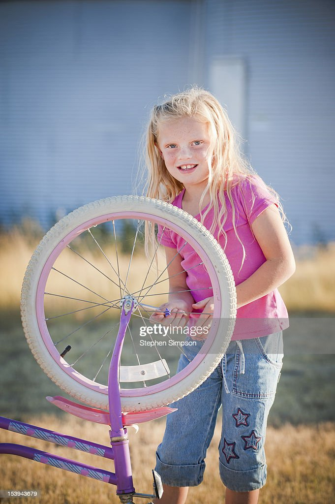 rural [farm] girl working on her bicycle : Stock Photo