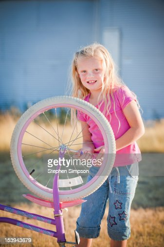 rural [farm] girl working on her bicycle : ストックフォト