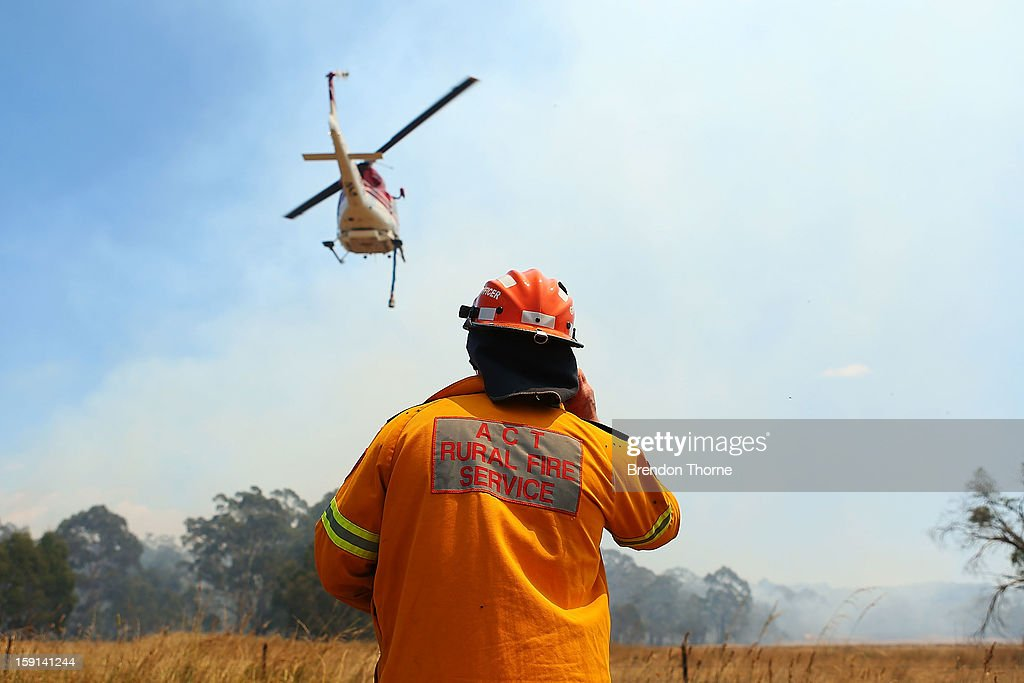 Rural Fire Service member watches water-bombing operations take place on a fire at Sandhills on January 9, 2013 in Bungendore, Australia. Temperatures cooled overnight offering relief to fire fighters following yesterday's heat wave recording temperatures of over 40-plus degrees across the state. Crews continue to fight blazes today, taking advantage of the improved conditions ahead fire danger conditions predicted later in the week.