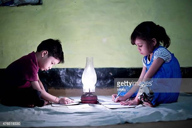 Village fille et garçon à étudier dans la Lampe d'éclairage